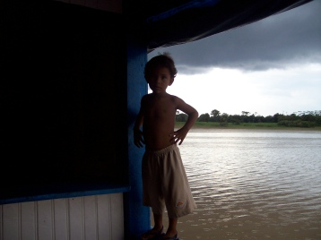 Cute boy on the Amazon after a torrential downpour